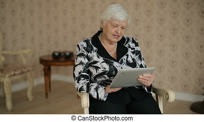 Senior Woman Uses Tablet PC - Senior woman using tablet PC...