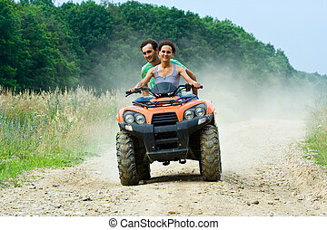 Couple riding ATV - Woman riding an All Terrain Vehicle...