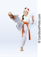 With orange belt girl in the cap of Santa Claus strikes a blow