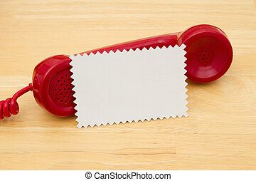 A retro red phone with note card