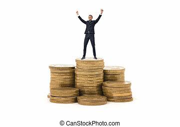 Businessman standing on stack of coins with his hands up in...