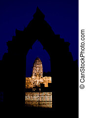 Iluminated Stupa under a dark blue night sky view through a stone gate in Ayutthaya. Ayutthaya city is the capital of Ayutthaya province in Thailand. Its historical park is a UNESCO world heritage.