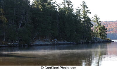 Mist rises from Algonquin lake in fall - A Mist rises from...