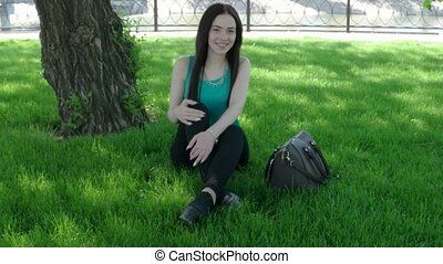 Pretty woman sitting on green grass with fashion handbag and looking to camera