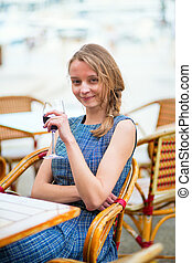 Young French woman drinking red wine in an outdoor cafe of...