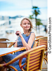 French woman drinking red wine in a cafe of Cannes - Young...