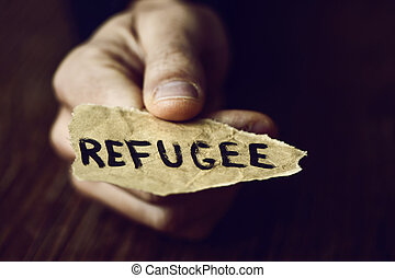 piece of paper with the word refugee - closeup of the hand...