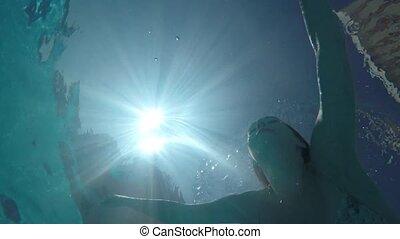 Beautiful slim woman in bikini swim in swimming pool -...