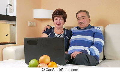 Happy senior man and a woman watching the movie on the laptop. They hug and discuss what is happening on the screen.