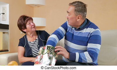 Happy senior man gives a woman's gift in package. He pulls out a pearl necklace and trying on her neck. Husband and wife in a beautiful house in Christmas