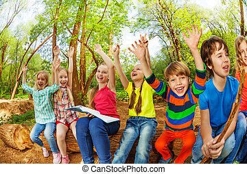 Cute kids sitting on the log with their hands up - Portrait...