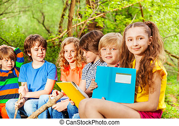 Group of happy kids sitting with books in the park