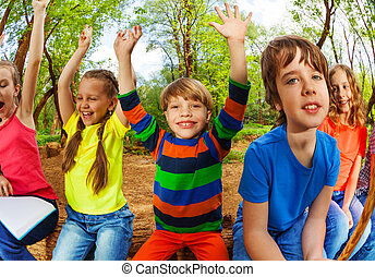 Smiling kids in summer forest with their hands up
