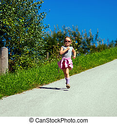 Cute little girl running on the road, energy concept