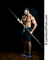 Gym iron bar as a spear. - Young slim fit athlete holding...