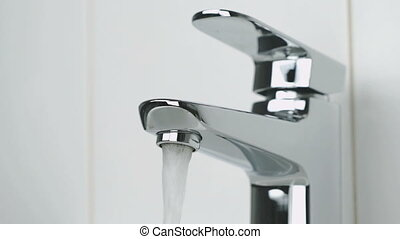 Flow of water is pouring from the stylish faucet - The...