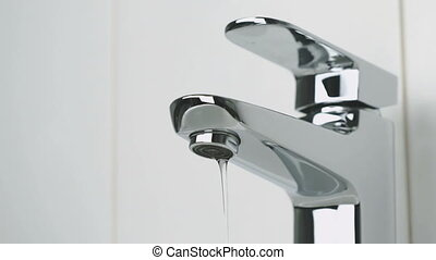 Weak stream of water pouring from the chrome tap - The...