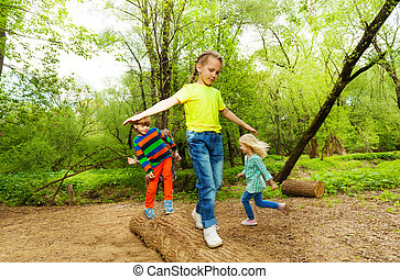 Kids standing on a log and balancing in the forest -...