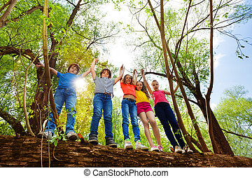 Happy kids standing on fallen tree in the forest - Five...