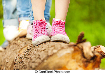 Children's feet in pink sneakers standing on a log -...