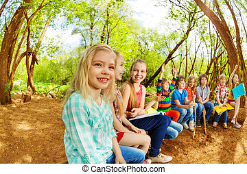 Happy kids sitting on a log in the summer camp - Big group...