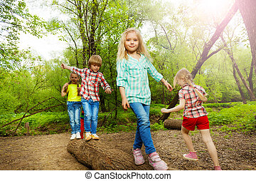 Happy kids walking on log and balancing in forest - Happy...