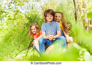 Cute kids sitting on a log in the summer park - Portrait of...