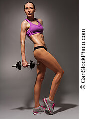 Full height portrait of fit woman with dumbbell