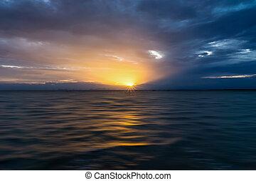 Cloudscape scene and rainfall with sunlight. Idea: Un-focus...