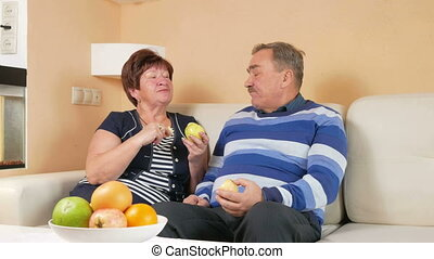 Senior couple resting at home on the couch and eat apples. On the table is a plate of different fruits. The husband and wife talk to each other.