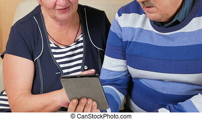 Happy senior man and woman talking on tablet PC at home with...