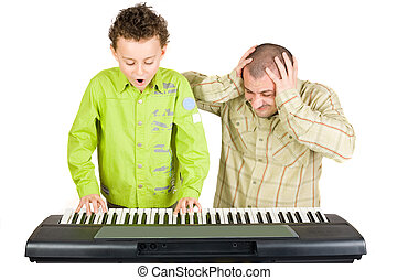 Kid playing piano badly - Schoolboy playing badly at the...