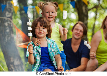 Two cute kids with roasted marshmallow at campsite