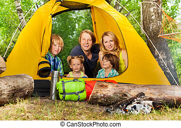 Happy young family relaxing inside tent in woods