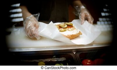 Hands of a worker prepare sandwich vintage looking shot with...
