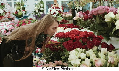 Beautiful girl with long hair choose a bouquet in the flower...