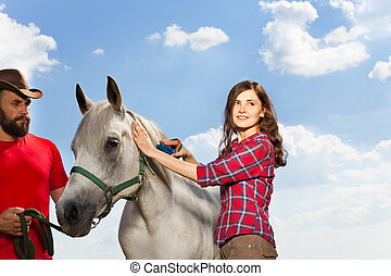 Portrait of pretty woman brushing her white horse - Portrait...