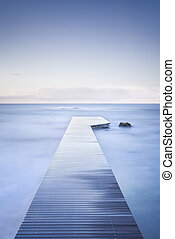 Wooden pier, rocks and calm sea on long exposure. - Wooden...