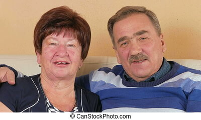 Happy senior man and woman making video call at home with...