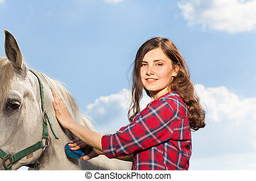 Portrait of young woman brushing a beautiful horse -...