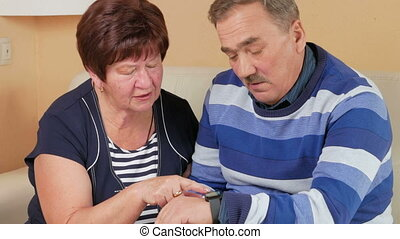 Senior couple checking a message on smart watch at home on the couch. They came to discuss the message. Wife touches the screen. The man has a mustache