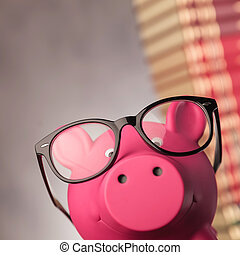 closeup of a piggy bank wearing glasses near books - closeup...
