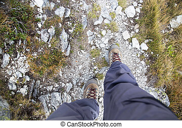 Woman legs with hiking boots on mountain path.Top view