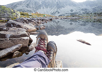 Hiking.Woman legs with boots and mountain lake view