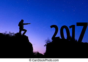 Silhouette of people on mountain point the finger at Text 2017 New year