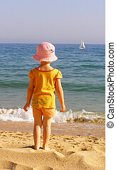 Lone sail - The little girl on the beach watching the lone...