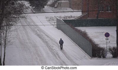 Man walks on road in snow