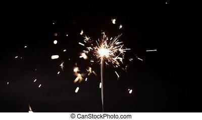 Lightening Christmas sparkler against dark background slow...