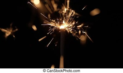 Lightening Christmas sparkler against dark background slow...
