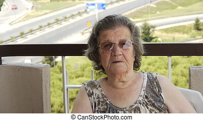 Old retired woman laughing outdoors